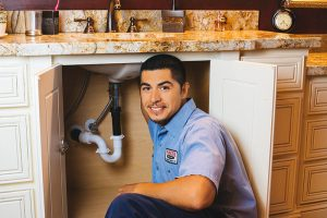 A Parker & Sons plumber unclogging a drain in a Phoenix home