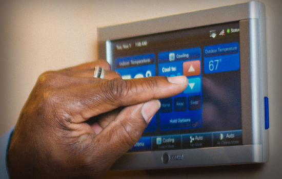A hand programming a digital thermostat