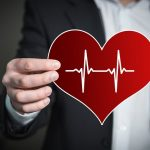 Man holding the outline of a healthy heart