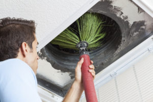 Man cleaning air ducts in home