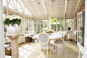 A bright, sunny screened-in porch with potted plants