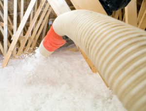 Insulation being blown into an attic