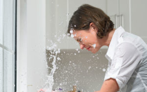A woman being sprayed in the face by a leaking fawcet