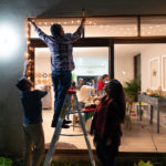 Three adults hanging white Christmas lights outside a window