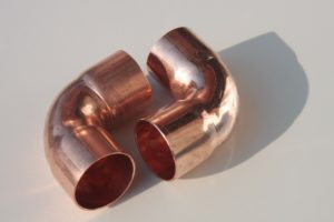 A pair of 90 degree copper pipe joints